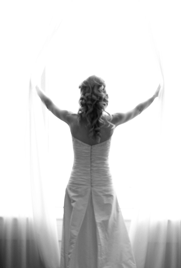 bride opening curtains wedding day photography